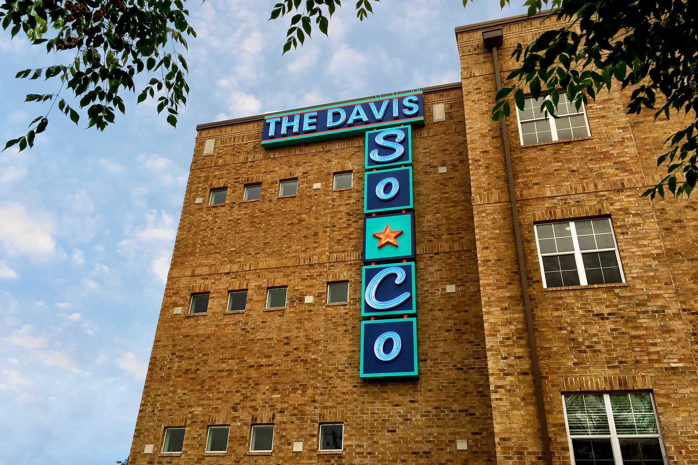 The Davis Soco Urban Industrial Illuminated Neon Wall Identity Sign During the Day